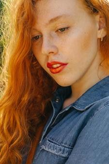 Nahaufnahme-straßenporträt des schönen roten behaarten jungen modells, das im sonnenglanz aufwirft