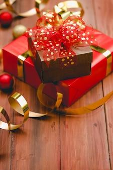 Nahaufnahme studioaufnahme eines kleinen braunen geschenks mit goldenem punkt auf roter schleife, die auf einer großen, mit papier umwickelten schachtel auf einem dunkelbraunen holztisch mit glänzenden, glänzenden weihnachtskugeln mit dekorativen kugeln platziert ist.