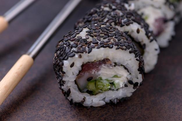 Nahaufnahme sushi-rolle mit lachs und schwarzem sesam