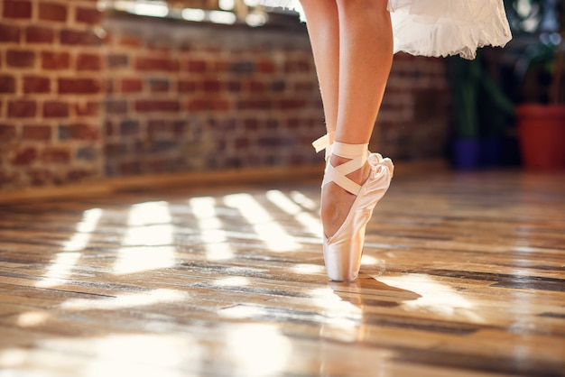Nahaufnahme tanzende beine der ballerina, die weiße spitzenballettschuhe in der tanzhalle tragen.
