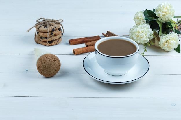 Nahaufnahme tasse kaffee mit blumen, zimt, verschiedene arten von keksen auf weißem holzbrett hintergrund. horizontal