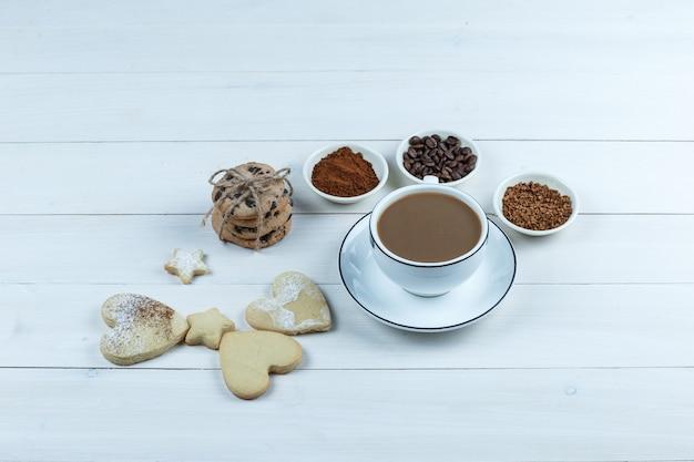 Nahaufnahme tasse kaffee mit kaffeebohnen, instantkaffee, kakao, verschiedene arten von keksen auf weißem holzbrett hintergrund. horizontal