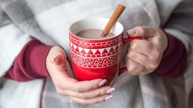 Nahaufnahme tasse tee, kaffee oder kakao weibliche hände halten auf pastellschal hintergrund