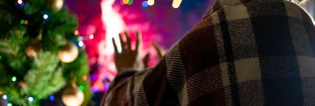 Nahaufnahme teenager entspannende kühlen unter der decke in der nähe von warmen kamin zu hause in einer winternacht.