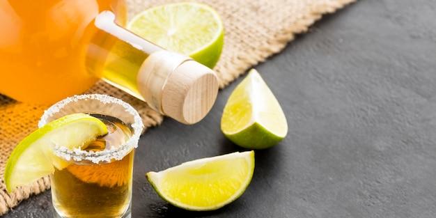 Nahaufnahme tequila schuss und limettenscheiben mit flasche