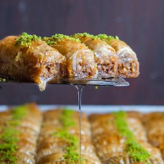 Nahaufnahme türkisches baklava-dessert aus dünnem gebäck, nüssen und honig
