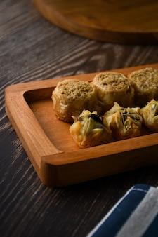 Nahaufnahme türkisches baklava süßes gebäck auf holztablett