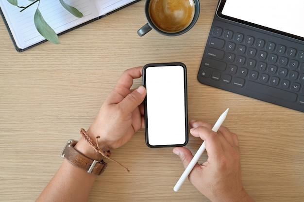 Nahaufnahme und draufsicht des mannes, der mobilen smartphone auf hölzernem schreibtisch des büros verwendet