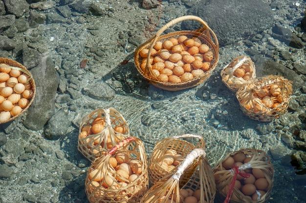 Nahaufnahme und ernte hühnereier im korb von touristen gekocht in mineral- und natürlichem heißem wasser im chae son nationalpark, lampang, thailand.