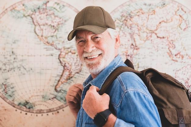 Nahaufnahme und porträt einer reifen frau, die trekkingkleidung mit einem rucksack auf dem rücken trägt - porträt eines aktiven rentners, der die kamera anschaut und mit einer hemisphäre oder einer karte im hintergrund lächelt