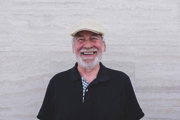 Nahaufnahme und porträt eines reifen mannes, der in die kamera schaut und lächelt - glücklicher kaukasischer senior, der allein genießt und spaß hat