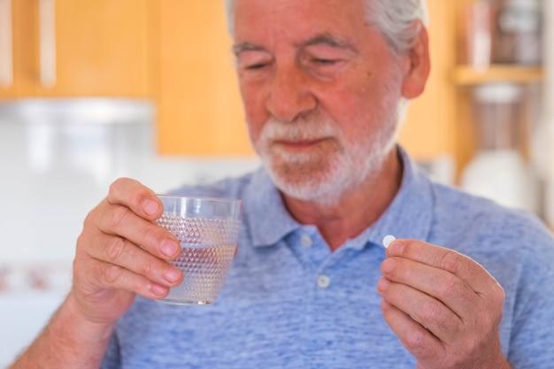 Nahaufnahme und porträt eines reifen mannes oder senioren, der medikamente und kissen mit einem glas wasser nimmt - kranker und schmerzender rentner