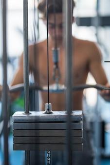 Nahaufnahme und porträt von gewichtheben und starkem mann im hintergrund, der eine barr hält, die übung macht, um seinen körper aufzubauen und gesund und fit zu sein