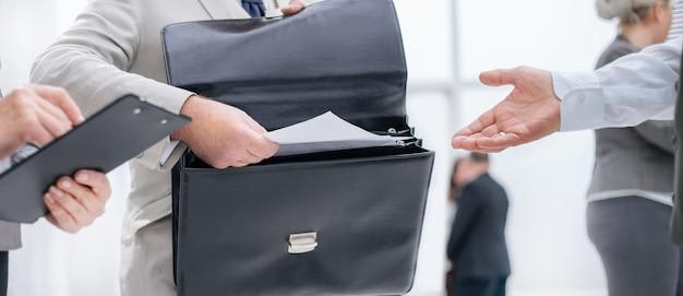 Nahaufnahme. unternehmer, der dem bankangestellten dokumente übergibt. geschäftskonzept