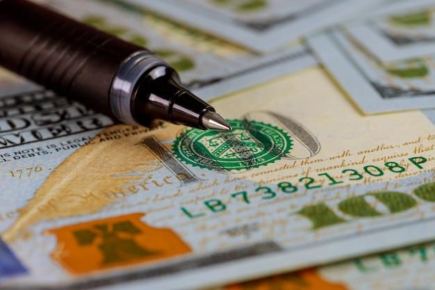 Nahaufnahme us-dollar-banknoten mit kugelschreiber auf dollar-banknoten