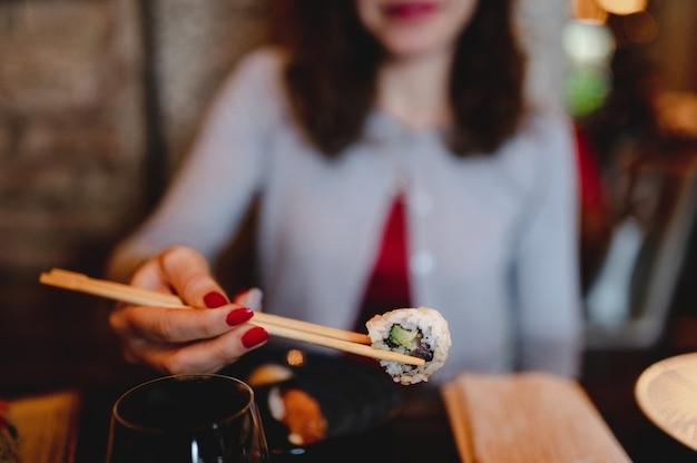 Nahaufnahme verschwommene frau, die traditionellen japanischen sushi-rollenlachs mit avocado hält, die zwischen essstäbchen gelegt wird