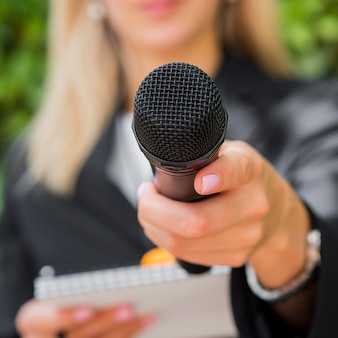 Nahaufnahme verschwommener journalist und mikrofon