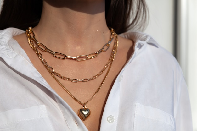 Nahaufnahme viele elegante goldketten mit herzformanhänger auf modell im weißen hemd, metallhalskette