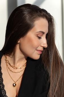 Nahaufnahme viele moderne goldketten mit herzformanhänger auf kaukasischer mädchenbrünette mit langem haar, metallhalskette