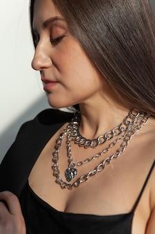 Nahaufnahme viele moderne silberketten mit herzformanhänger auf kaukasischer modellbrünette mit langem haar, metallhalskette, sonnenlicht