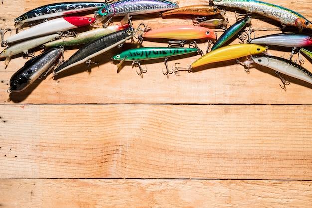 Nahaufnahme vieler bunter fischenköder auf hölzernem schreibtisch