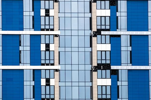 Nahaufnahme vieler fenster auf einem blauen äußeren des modernen mehrfamilienhauses. für immobilien hintergrund.