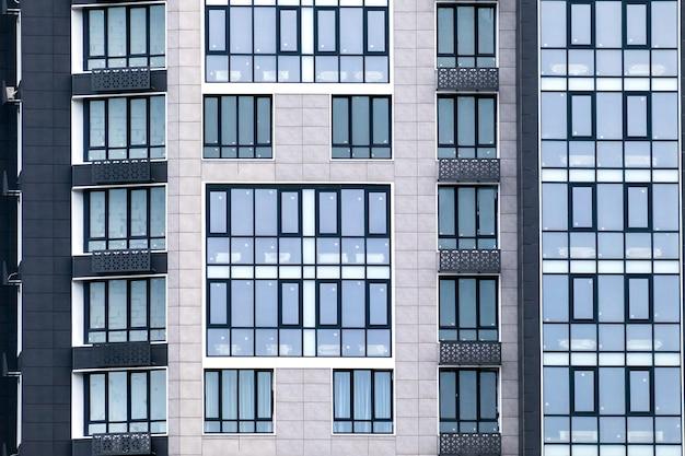 Nahaufnahme vieler fenster auf einer grauen fassade des modernen mehrfamilienhauses. für immobilien hintergrund.