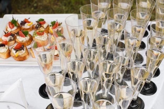 Nahaufnahme vieler flöten champagner oder anderer kohlensäurehaltiger getränke mit toast mit gemüse und frischkäse bei hochzeitsfeier oder bankett. festlicher empfang.