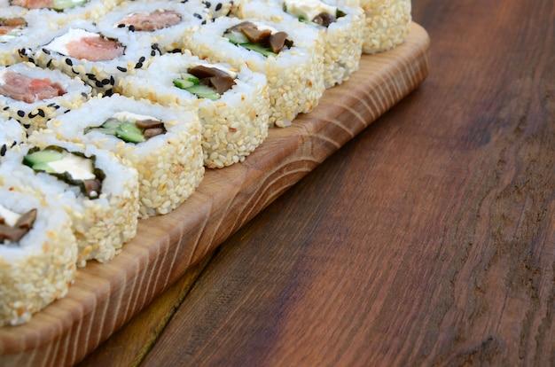 Nahaufnahme vieler sushirollen mit verschiedenen füllungen liegen auf einer holzoberfläche. makroschuß des gekochten klassischen japanischen lebensmittels mit einem kopienraum