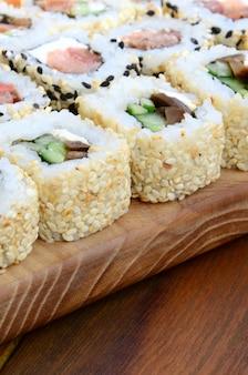 Nahaufnahme vieler sushirollen mit verschiedenen füllungen liegen auf einer holzoberfläche
