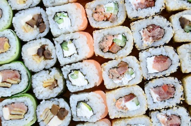 Nahaufnahme vieler sushirollen mit verschiedenen füllungen.