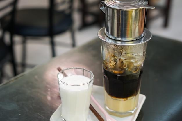 Nahaufnahme-vietnamesischer tropfenfänger-kaffee und eisbecher gedient mit milch, gefror schwarzer kaffee.