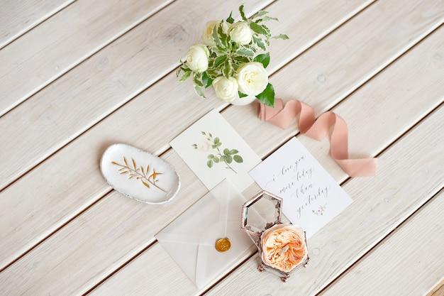 Nahaufnahme vintage hochzeit schmuckschatulle für eheringe auf einem holztisch mit einer grußkarte und einer blumenvase.