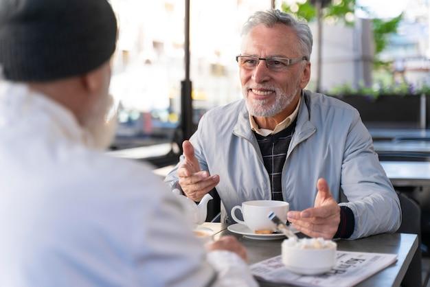 Nahaufnahme von alten freunden, die am tisch sitzen