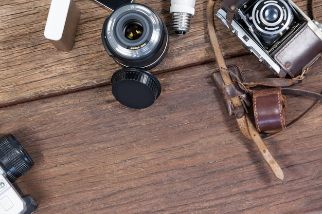 Nahaufnahme von altmodischen kameras, objektiv, glühbirne auf tisch