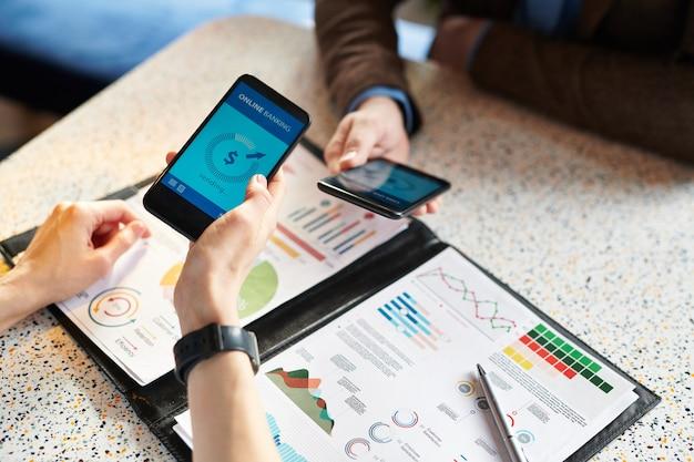 Nahaufnahme von analyseexperten, die mit diagrammen arbeiten und smartphones verwenden, während sie online-transaktionen über die mobile bank-app durchführen