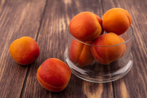 Nahaufnahme von aprikosen im glas und auf hölzernem hintergrund