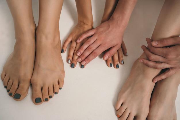 Nahaufnahme von armen und beinen hände mit lackierten nägeln hände und füße mit manikürenägeln verschiedener sch...