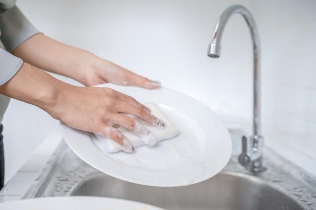 Nahaufnahme von asiatischen frauen wäscht teller in der küche mit ihrem spülschwamm.