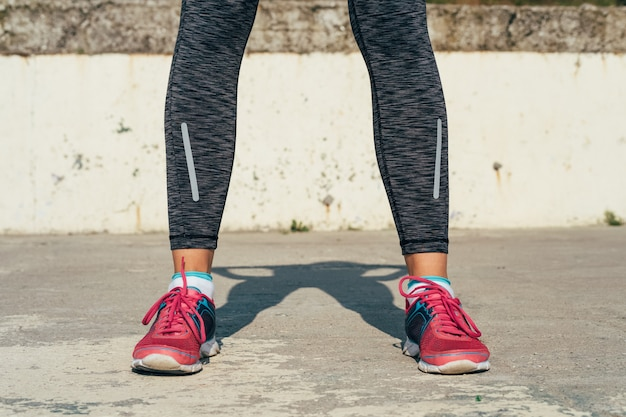 Nahaufnahme von athletischen weiblichen beinen in den roten turnschuhen auf einer konkreten auflage draußen im sonnenlicht