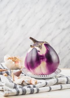 Nahaufnahme von auberginen- und knoblauchzehen auf kariertem mustergewebe