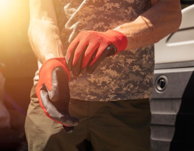 Nahaufnahme von automechanikern oder mechanikern, die handschuhe anziehen