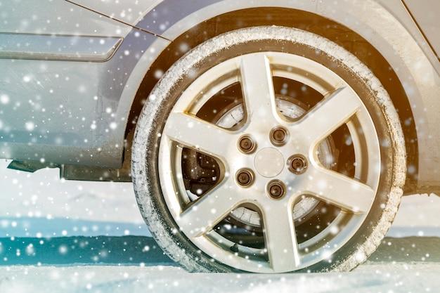 Nahaufnahme von autoradgummireifen im tiefen winterschnee. transport- und sicherheitskonzept.
