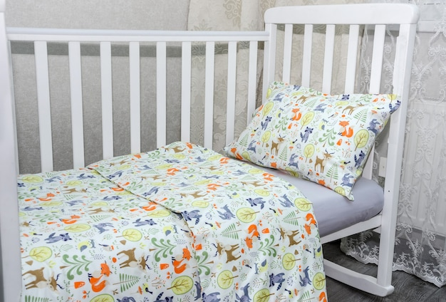 Nahaufnahme von babybett und kissen mit decke