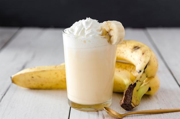 Nahaufnahme von banane smoothie mit goldenem löffel