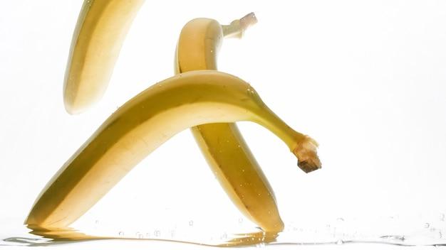 Nahaufnahme von bananen, die in klares wasser fallen