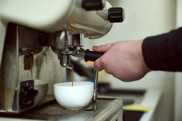 Nahaufnahme von baristas händen, die espresso in der professionellen kaffeemaschine zubereiten