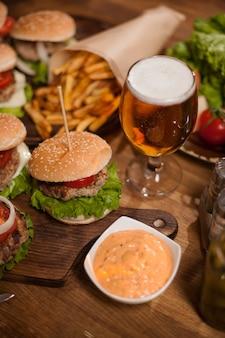 Nahaufnahme von beef burger und bier auf einem tisch im restaurant. leckerer imbiss. fastfood. pommes frittes.