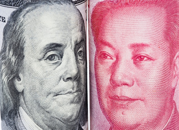 Nahaufnahme von benjamin franklin und mao tse tung vom us-dollar und von china yuan-banknoten.