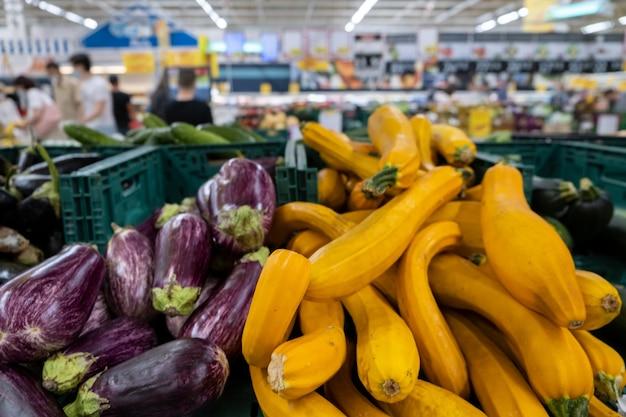Nahaufnahme von bio long purple aubergine oder aubergine solanum melongena und kürbis auf dem markt.